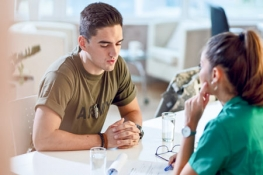 Female nurse consulting man in army shirt