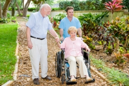 Nurse pushing an older lady in a wheel chair with her husband walking beside them